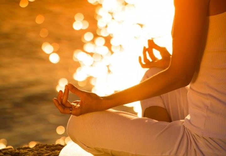 Woman sitting by lake meditating.