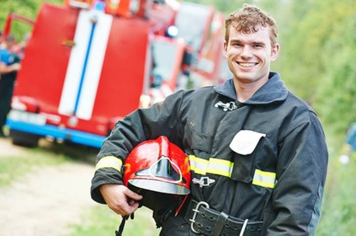 Young smiling fireman firefighter in uniform in front of fire engine machine