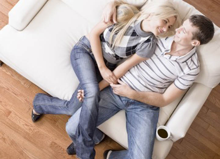 Beautiful woman snuggling with boyfriend on couch.