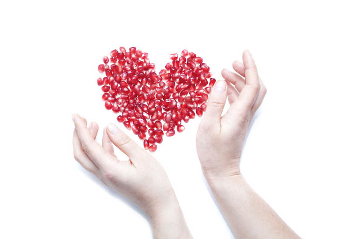 A woman's hands surrounding red seeds in the shape of a heart, representing planting the seeds of love.