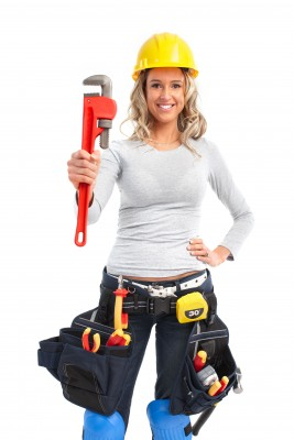 A young woman holding a wrench with a tool belt on looking to fix her man.