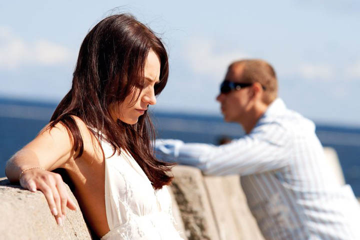 A beautiful woman on a pier with her boyfriend in the background, upset because he won't commit.