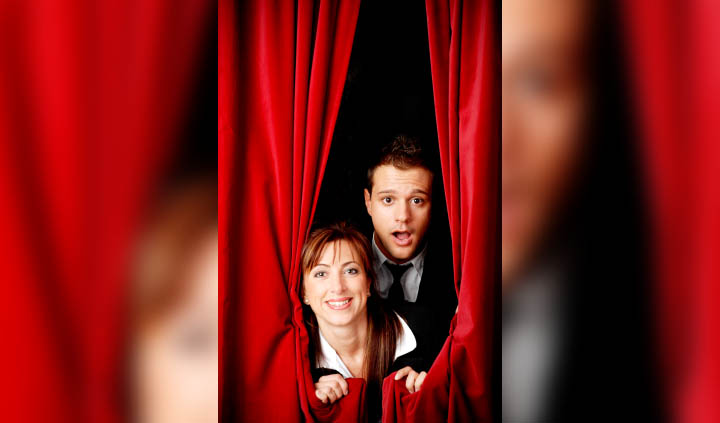 A man and a woman peek out from behind a curtain on a stage.