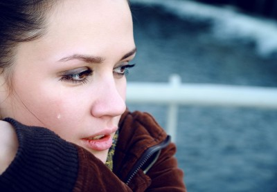 A beautiful woman is crying after her breakup, thinking of the song A Beautiful Goodbye, after having her heart broken.