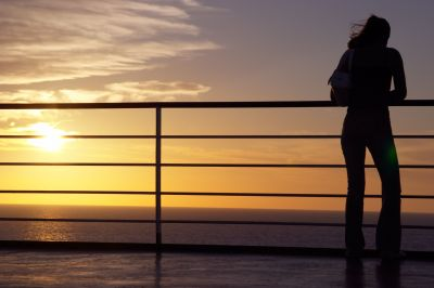 An attractive woman is watching the sunset from the deck of a ferry boat, realizing that tomorrow is a new day.