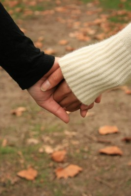 Real Love. Real Love never leaves you hanging. Real Love never leaves you guessing. Real love never hurts. A man and woman are holding hands walking through an autumnal field of fallen leaves.