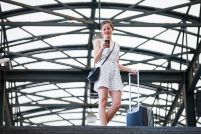 At some point, every long-distance relationship needs to have two people be together to see if this is really going to be the relationship it promises to be. A beautiful woman is walking through the airport looking at her phone dialing her long distance relationship boyfriend hoping for commitment.