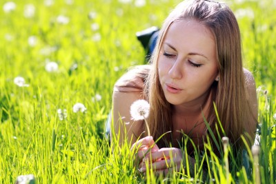Once you make a habit of noticing all of the little things there are to be grateful for your entire life will change for the better. A beautiful woman is lying in the grass looking at a dandelion thinking of  everything she has to be grateful for.