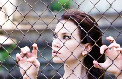 We think we need to be perfect, or at least somewhere close. We have so little grace for ourselves, for what we've been through, where we've come from.  A beautiful woman is looking out from behind a chain link fence, symbolic of her own beliefs that are keeping her from having the relationship she wants.