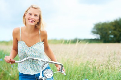 It begins with getting in touch with who you are and all that you have to offer. A beautiful woman is riding a bike in a field living life to the fullest.