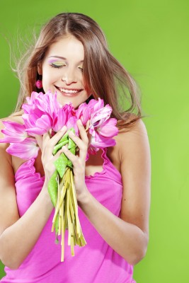 Loving yourself and recognizing all of the wonderful, valuable, and lovable qualities that make you the beautiful person that you are is the first step to having the kind of love in your life that you've been longing for. A beautiful woman is celebrating herself by giving herself a bouquet of flowers.