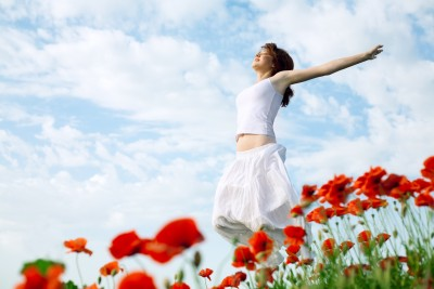 The way our lives have worked out, and the route our journeys have taken on the road to finding ourselves and the love in our lives, is all part of the life that we are meant to live and are living now. A beautiful woman is embracing her life with arms outstretched in a field of red flowers.