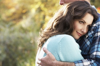 It's time to define for yourself exactly what commitment looks like to you. A beautiful woman is embracing her man in a committed relationship after he has professed his commitment to her in an autumn woodland setting.