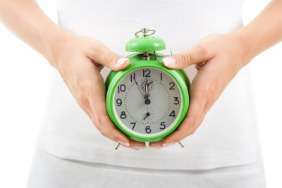 A woman who is concerned that her biological clock is ticking away and she hasn't yet found her Mr. Right is holding a biological clock near her belly.