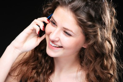 A beautiful brunette woman is smiling and talking on her cell phone trying to keep an open mind