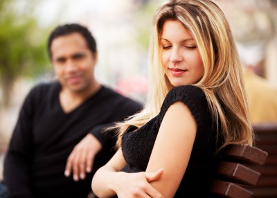 A beautiful blond woman in a black sweater sits near a man on a park bench looking away slyly, not only playing hard to get, but being hard to get.