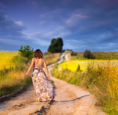 A beautiful woman is walking down a path in a field of yellow flowers, representing her journey towards learning to love herself and finding true love.