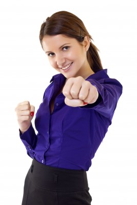 A beautiful brunette woman in a blue blouse and black skirt is punching her fist in the air, showing that she is strong and confident and is ready for commitment.