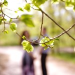 A man telling a woman he just wants to be friends. They are standing in a park on a path, out of focus, with the camera looking through branches.