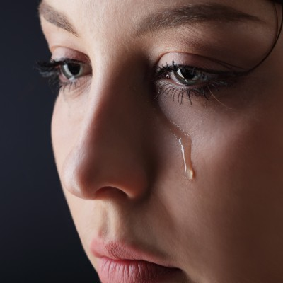 A close-up of the face of a beautiful woman with a tear rolling down her cheek. It's not your fault.