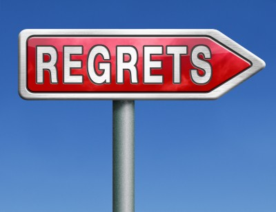 A large red sign against a background of blue sky reads: regrets.