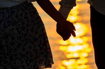 A happy couple holding hands at sunset near the ocean, realizing what really matters.