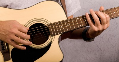 A man plays acoustic guitar while singing about commitment to his girlfriend who wants a commitment.