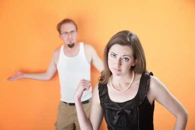 A beautiful woman is pointing at her slacker boyfriend wondering if she needs to move on. He is wearing a white tank top standing against an orange wall.