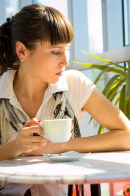 A beautiful woman sits alone in a coffee shop hoping he will call but he hasn't called.