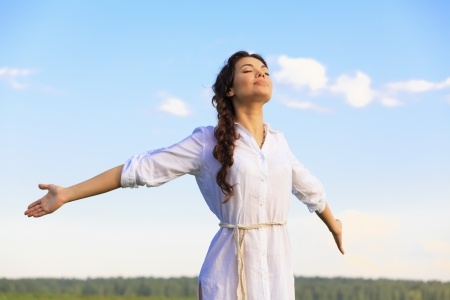 A beautiful woman is standing in a field with her arms outstretched, looking towards the sky as she starts to dream big.