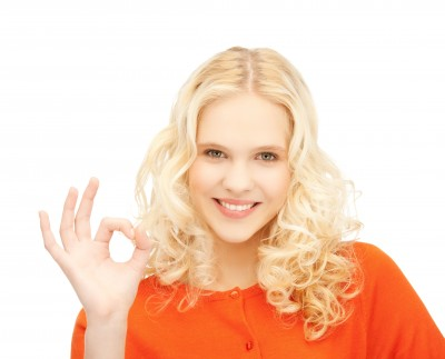 A beautiful woman is giving the OK sign because she's figured out what to look for in a guy. She is blond, wearing an orange blouse and standing against a white background.