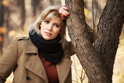 A beautiful blond woman leans against a tree during autumn, thinking why she stays in the relationship she is in.