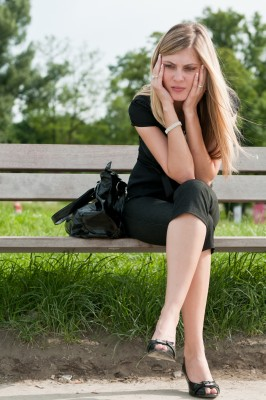 A beautiful blond woman sits on a park bench with her face in her hands because she is feeling rejected.