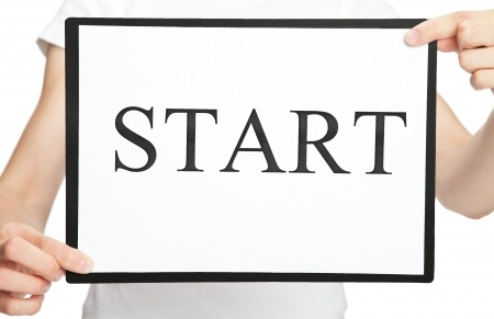 A woman is holding a start sign indicating that you have to start where you are.