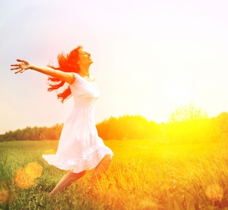 A beautiful woman runs through a sunlit field with her arms outstretched, believing in love
