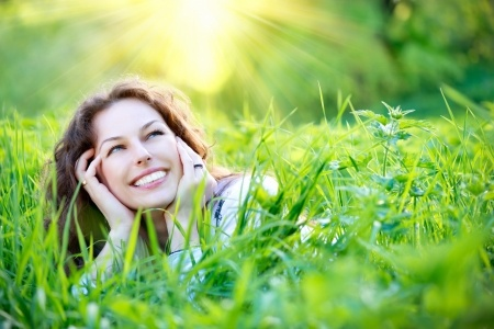 A beautiful woman is laying in a field of grass smiling knowing that her mindset of confidence is making her more confident and improving her love life.
