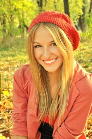 A beautiful woman is smiling in an autumn scene, thinking about 3 things to be thankful for in her love life.