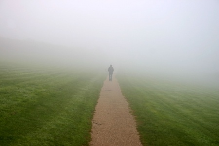 A man is walking down a path through a green field into misty fog representing a man who disappeared without an explanation from his relationship.