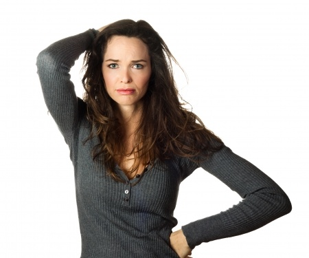 A beautiful brunette woman in a gray sweater has one hand on her head and one hand on her hip, sad and confused wondering if her expectations of her boyfriend are reasonable.