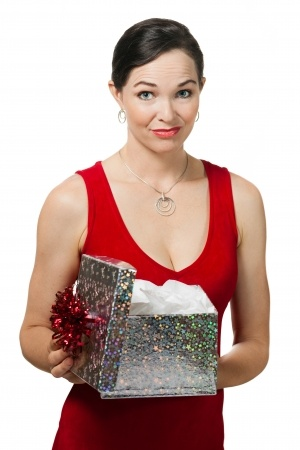 A beautiful woman in a red dress is disappointed as she opens a Christmas gift and realizes that is is not the ring signifying a commitment that she really wanted when she really wanted a committed relationship.