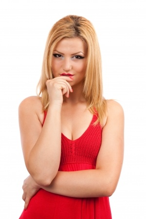"A beautiful blonde woman in a red dress looks serious with her hand near her lips as she wonders ""am I wasting my time?"" on a relationship with a guy that won't commit."