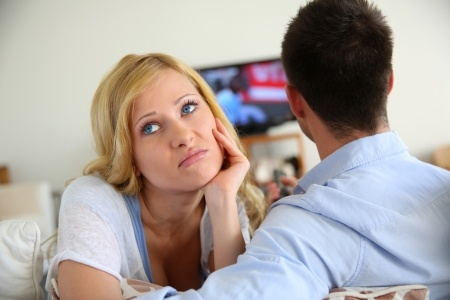 A beautiful blond woman is upset at her boyfriend because he won't commit, as he just watches TV and can't talk about it.