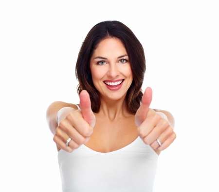 A beautiful brunette woman in a white t-shirt against a white background is holding her thumbs up as she knows that her only new years resolution this year is to find love.