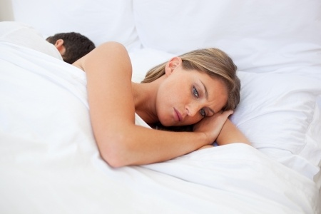 A beautiful blond woman lies in bed with her boyfriend wondering am I just a booty call