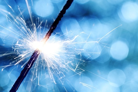 Image of a sparkler against a blue bokeh background representing the truth about the spark in a relationship.