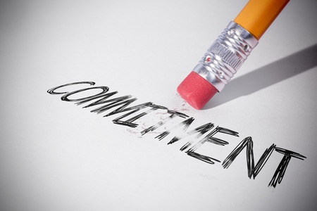 A pencil erasing the word commitment written on white paper, symbolizing a man who suffers from commitment phobia and won't commit or make a commitment and is afraid of a committed relationship.