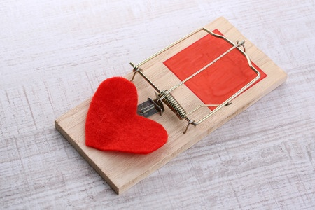 A mousetrap with a red felt heart representing the trap that many women fall into of comparing themselves to others.