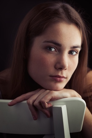 A beautiful woman leans her chin in her arm on a chair, thinking about why she was unable to set boundaries with her previous boyfriend.