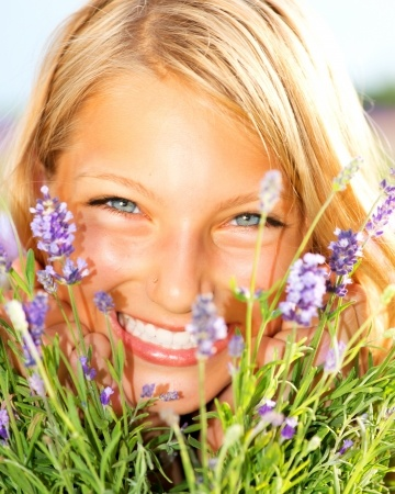 A beautiful woman is living and loving life as she looks through lavender flowers smiling and happy.
