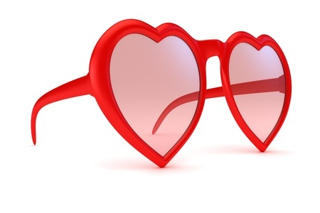 Falling in love too fast: A pair of rose colored glasses with heart shaped frames sits on a white table, indicating falling in love fast and hard.